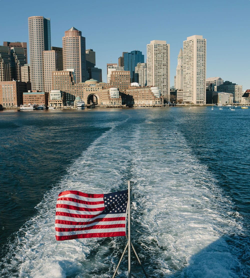 Boat wake with Boston cityscape in the background near Ora Seaport Apartments in Boston