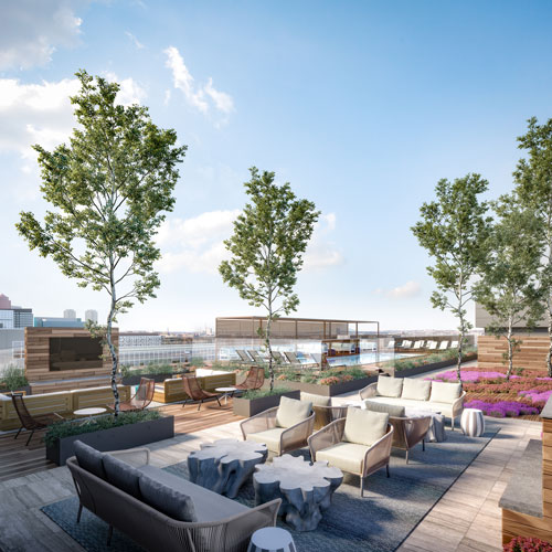 Apartment rooftop deck with decorative trees and a fireplace at Ora Seaport Apartments in Boston, MA