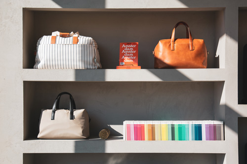 3 multi-colored handbags line a shelf at a retail shop near Ora Seaport Apartments in Boston