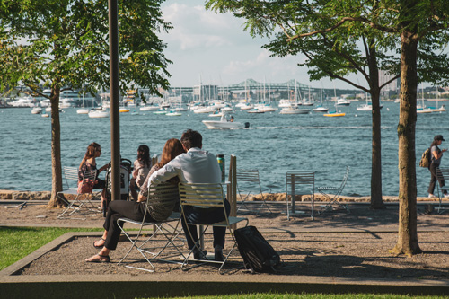 A man embraces a woman while sitting together at a waterside park near Ora Seaport Apartments Boston