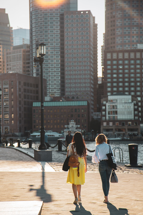 2 girl friends walk together on a dock in Boston Seaport near Ora Seaport Apartments in Boston