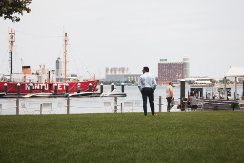 A man in business casual looks out over Boston Seaport near Ora Seaport Apartments in Boston