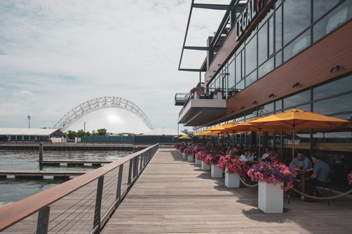 Outdoor waterside seating of Boston Seaport restaurant near Ora Seaport Apartments in Boston, MA