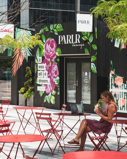 A woman sits alone at a group of red tables outside Parlr Lounge near Ora Seaport apartments Boston