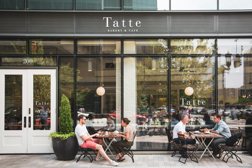 People enjoying outdoor seating at Tatte Cafe near Ora Seaport luxury apartments in Boston