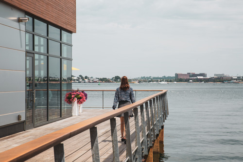 A woman walks along a waterside balcony near Ora Seaport luxury apartments in Boston, MA