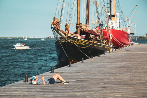 A person sunbathes on a dock next to a large galley ship near Ora Seaport apartments in Boston