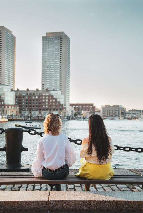 Two women sit together by the water in Boston Seaport near Ora Seaport luxury apartments in Boston