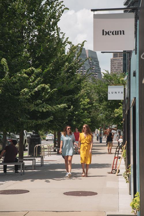 People utilizing a store-lined sidewalk in downtown Boston