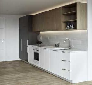 Kitchen with white and brown cabinets and black pantry