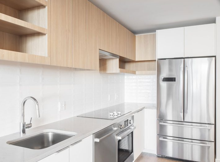 Thumbnail of stainless steel appliances in a white apartment kitchen