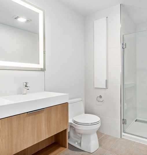 White bathroom with wooden cabinets and glass shower