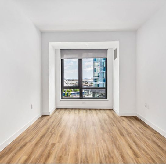 Empty apartment space with wood floors and white walls