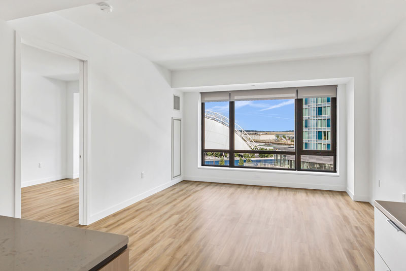 Empty living space with wood floors and city views
