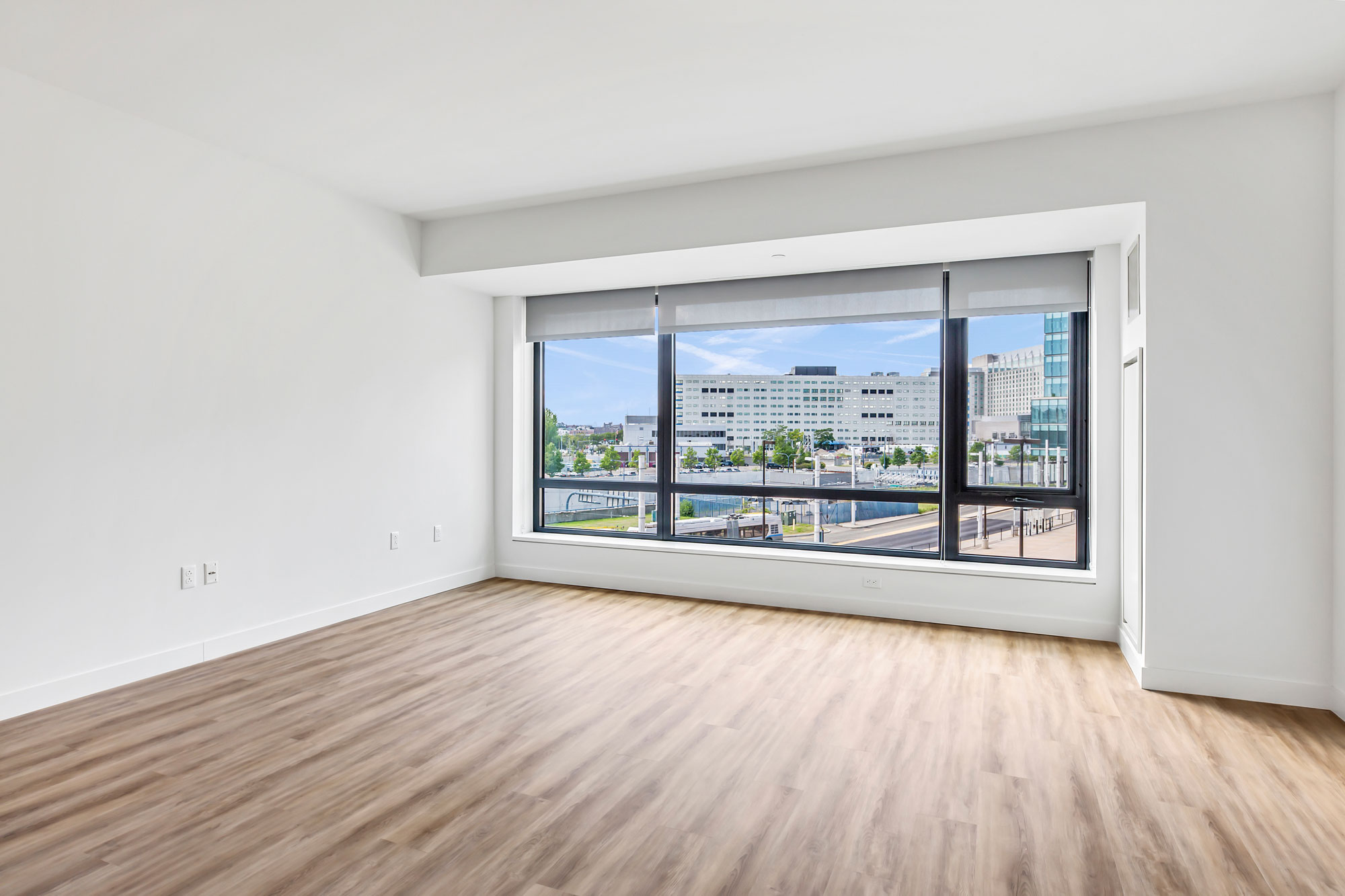 Empty living area with wood floors and large window with city view