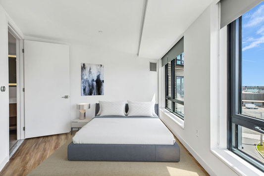 White bedroom with wood floors and large windows