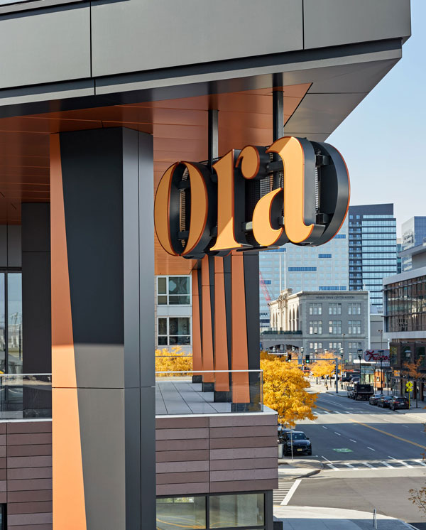 Orange Ora sign on 2nd story overlooking city street