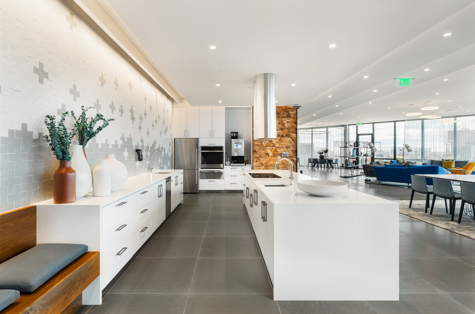 Modern common area kitchen with decorative white and grey brick wall