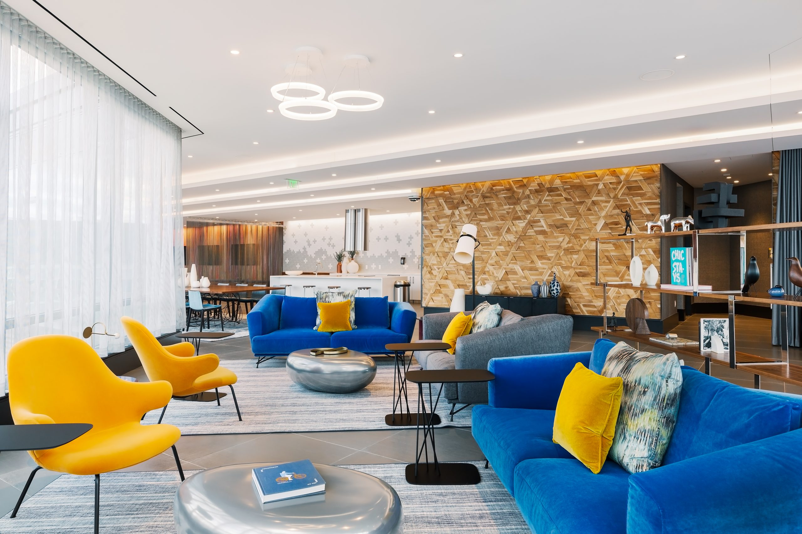 Blue and yellow themed common sitting area with couches and chairs