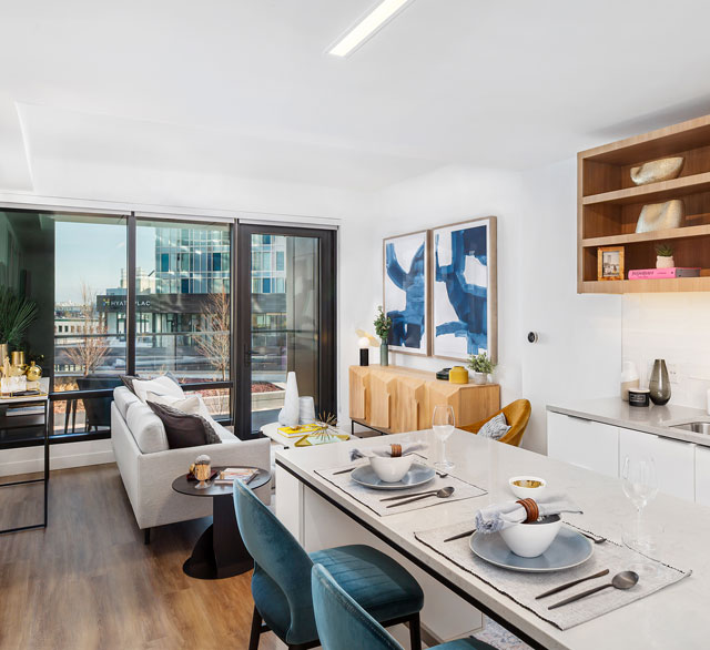 Open concept apartment kitchen and living area with glass patio door