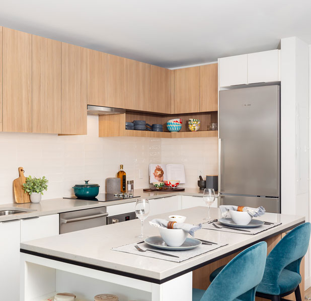 Apartment kitchen with white tile backsplash and island with blue chairs