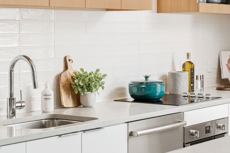 Kitchen with white counters and backsplash and stainless steel appliances