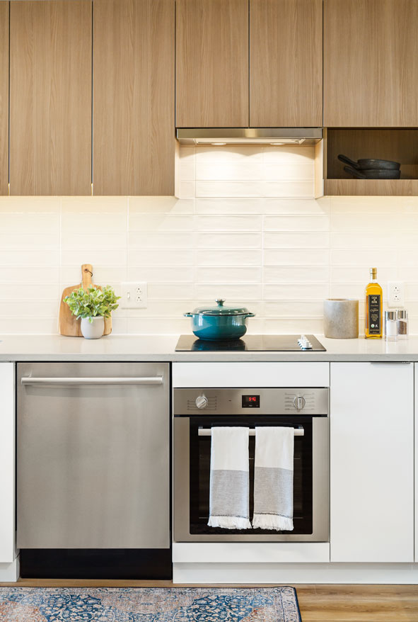 Apartment kitchen with stainless steel appliances and white counters