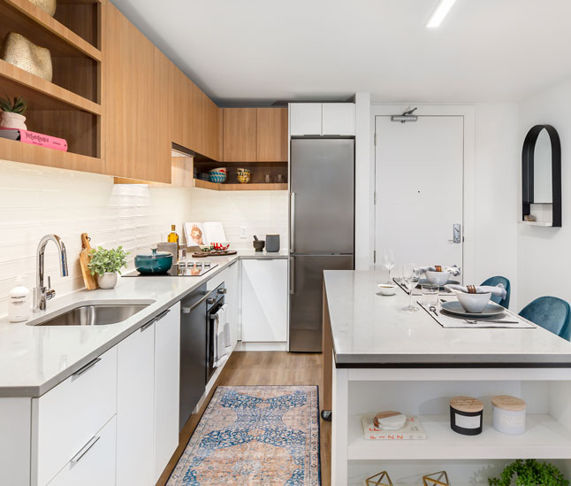 Apartment kitchen with white countertops and light wood cabinets