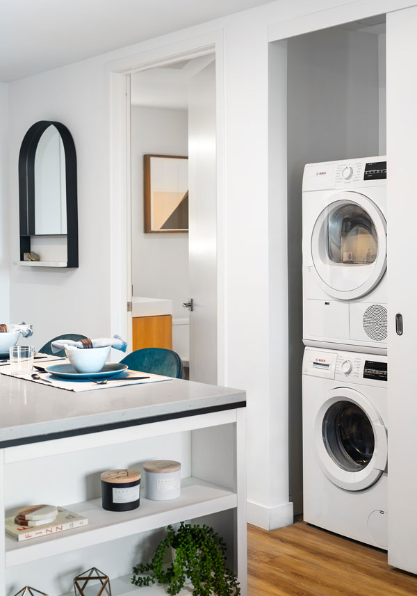 Apartment kitchen area with laundry room with stackable washer/dryer