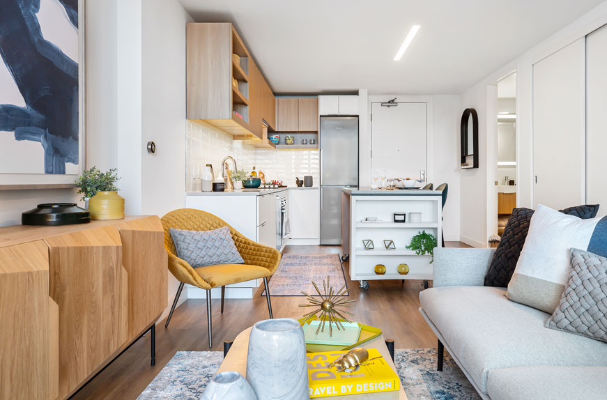 Open concept apartment living and kitchen area with wood floors