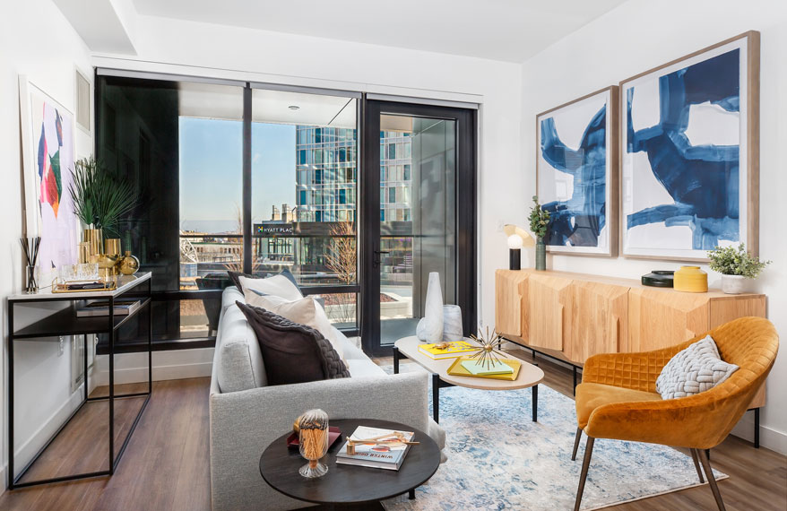 Apartment living area with wooden credenza and glass patio door