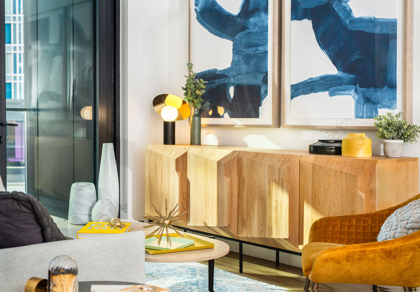 Modern living area with abstract art and light wood tones