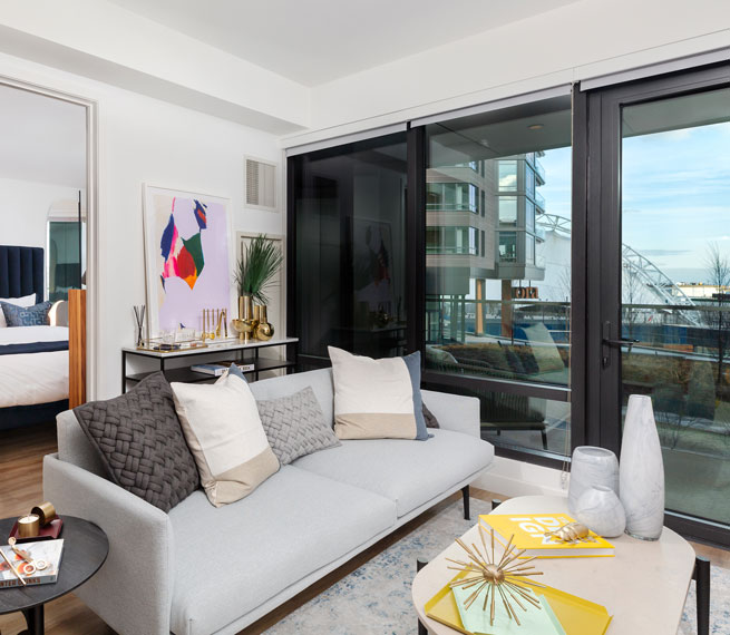 Apartment living area with sliding patio door and view into bedroom