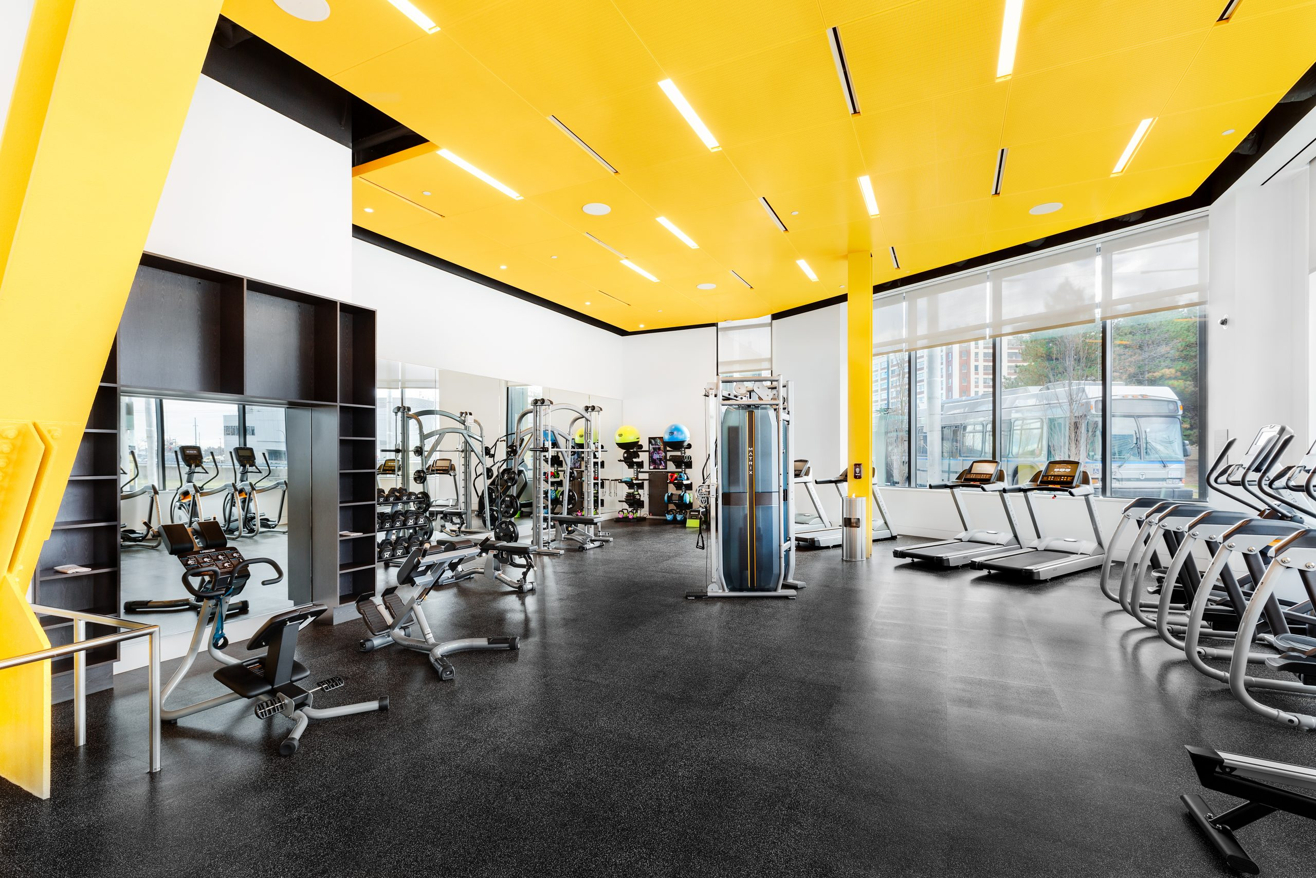 Gym with yellow ceiling and multiple exercise machines