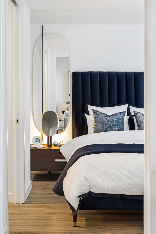 View into blue and white bedroom with large oval mirror