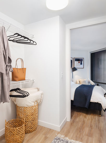 Walk-in closet looking into a bedroom with light wood floors