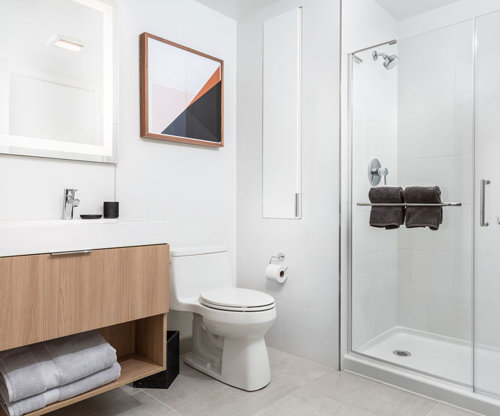 Modern bathroom with white tile walls and standing glass shower