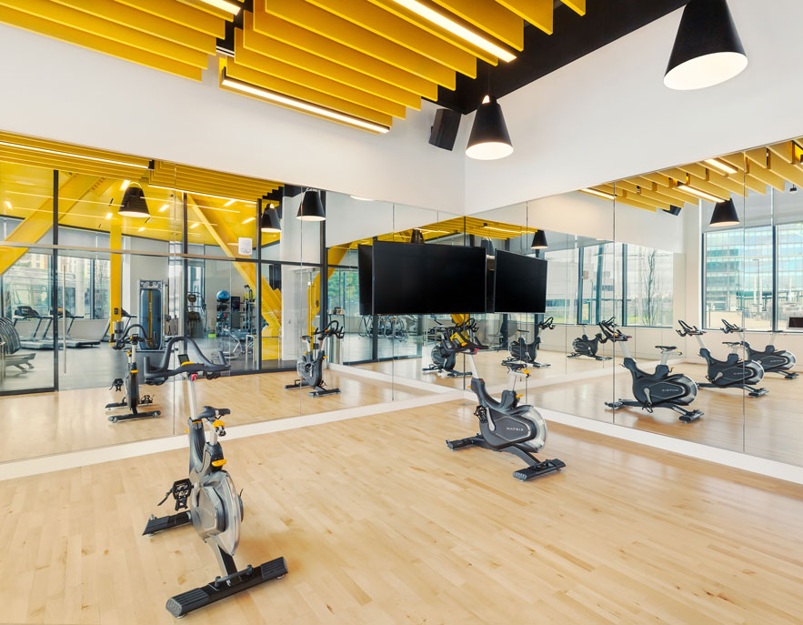 Cycling studio with mirrored walls and light wood floors