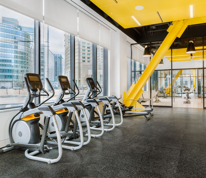 Modern style gym with yellow walls and black mat flooring