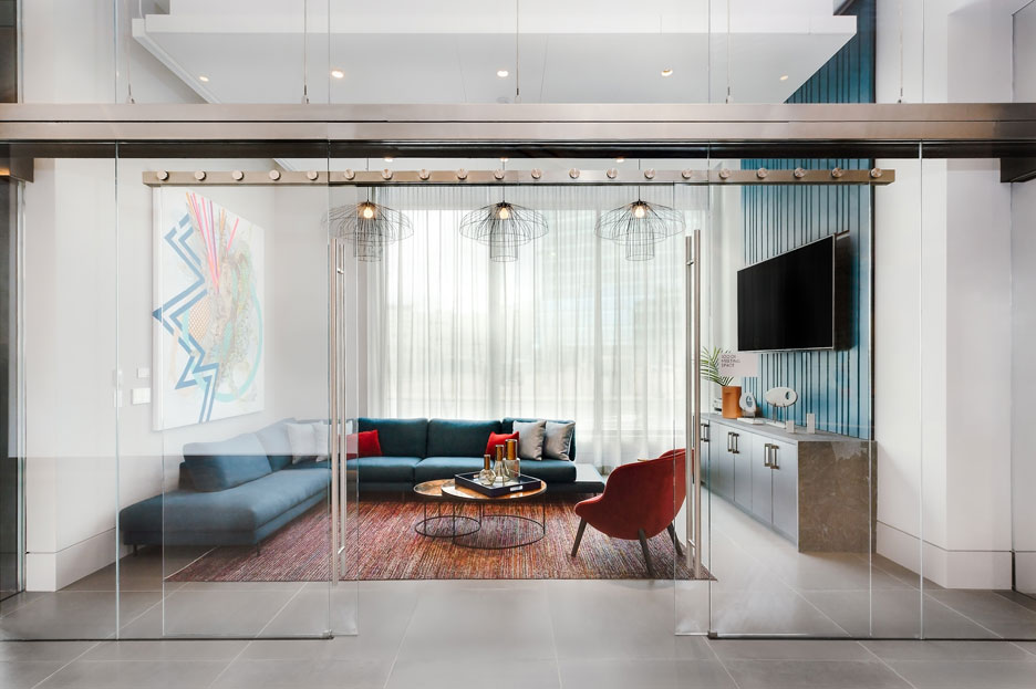 Glass room with blue couch sectional and wall-mounted TV